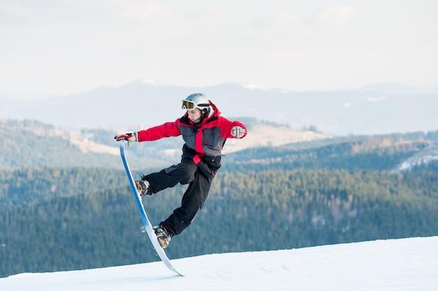 Huésped masculino en su tabla de snowboard en winer resort