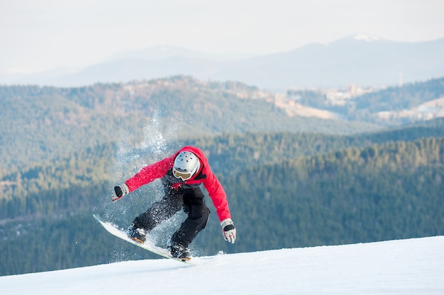 Huésped masculino en su tabla de snowboard en winer resort