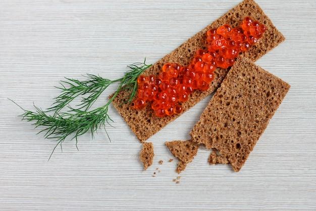 Huevas de caviar rojo en barra de pan sobre una mesa