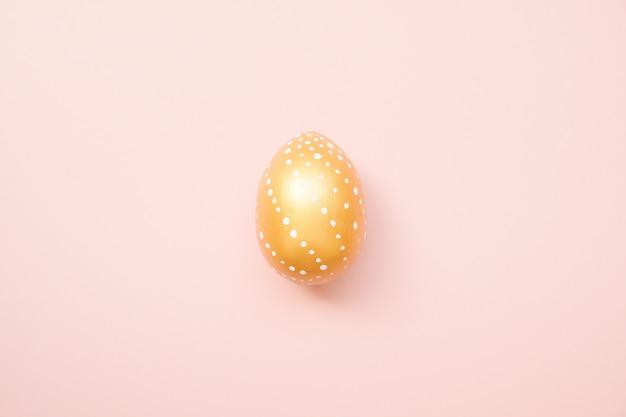 Huevo adornado de oro de pascua en fondo del rosa en colores pastel. feliz pascua tarjeta