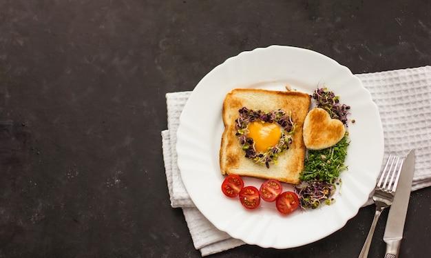 Huevo en un agujero de pan en forma de corazón, microgreens, comida sana desayuno, té, fondo negro