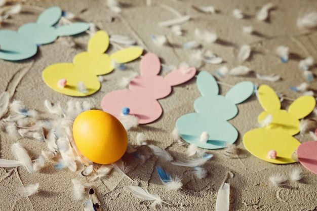 Huevo amarillo y garland con plumas y conejos de papel de colores. concepto de pascua. vista superior.
