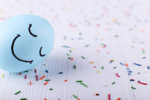 Huevo azul con sonrisas pintadas tarjeta de felicitación de pascua feliz.