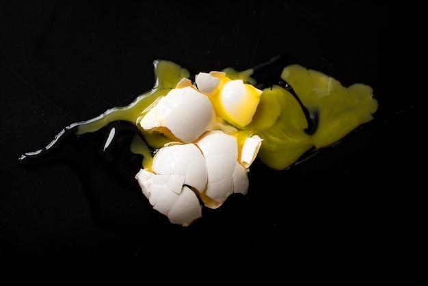 Huevo blanco quebrado en fondo negro. bandeja de huevos