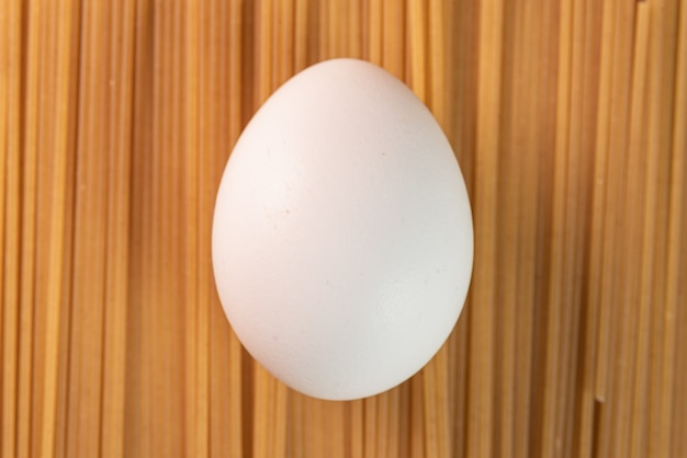 Huevo blanco sobre la pasta cruda