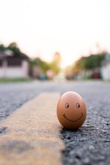 Huevo con la cara triste dibujada cerca de los felices en el camino. amenaza de depresión
