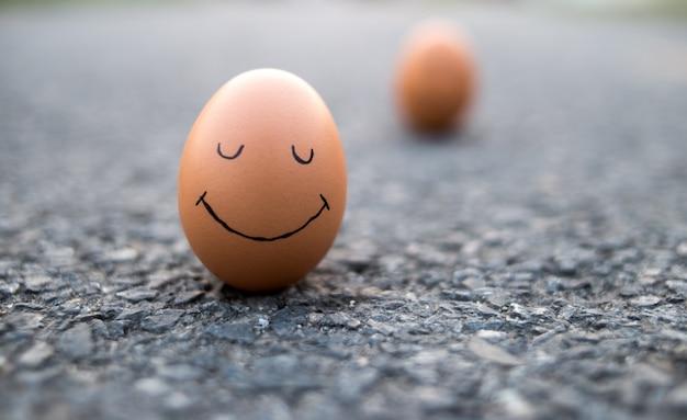 Huevo con cara triste dibujada cerca de felices en la carretera