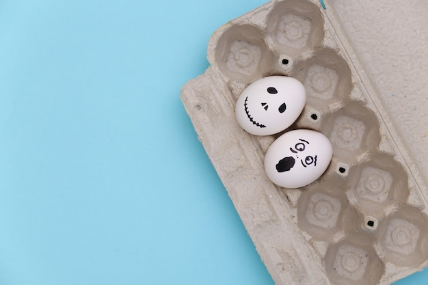 Huevo con caras de fantasmas aterradoras dibujadas a mano sobre fondo azul. vista superior