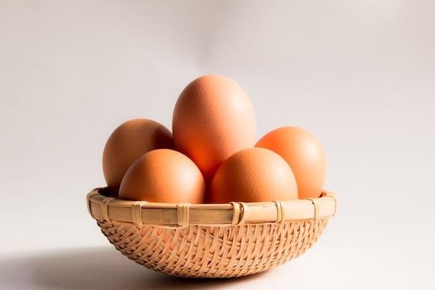 Huevo en cesta de mimbre sobre fondo blanco, huevos de pato en cestas.