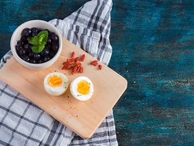 Huevo cocido con bayas en tablero de madera