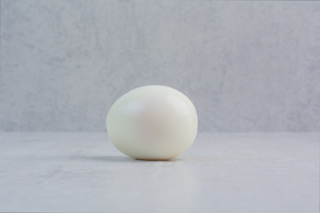 Un huevo cocido entero sobre fondo gris.