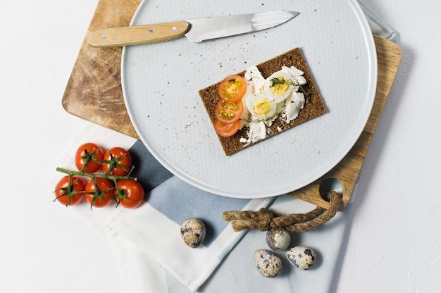Huevo de codorniz tostada. ingredientes tomates, huevo, queso, pan de centeno.