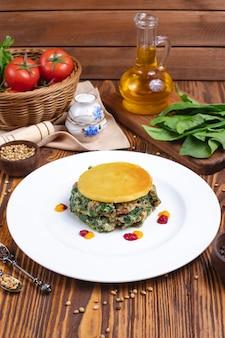 Huevo con costra de espinacas, arroz, tomate, especias, vista lateral