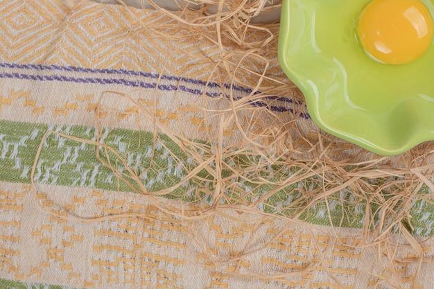 Huevo crudo en placa verde con heno sobre mesa de mármol.