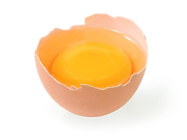 Huevo crudo se rompe en dos con yema y albúmina