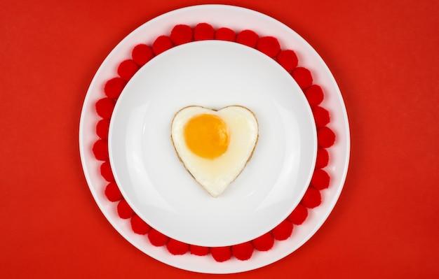 Huevo en forma de corazón desayuno festivo, almuerzo día de san valentín. sobre una mesa roja. lugar para su texto.