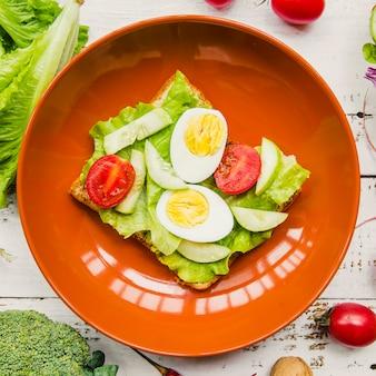 Huevo fresco y sandwich de verduras en un tazón