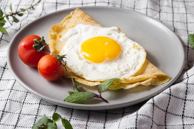 Huevo frito con crepe y tomates cherry