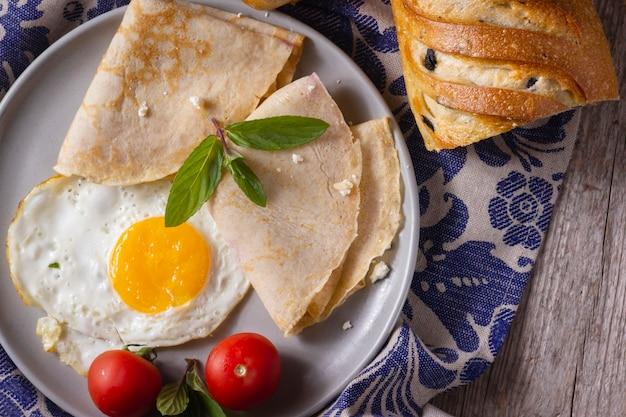 Huevo frito con crepes y tomates