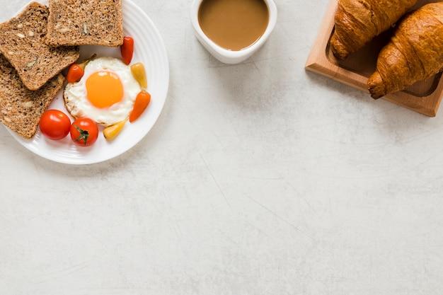 Huevo frito con cruasanes de pan y café con espacio de copia
