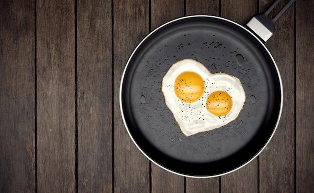 Huevo frito con dos yemas en forma de corazón en una sartén sobre madera