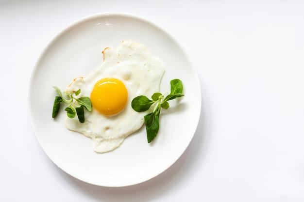 Huevo frito con ensalada verde en un plato blanco, aislado en blanco