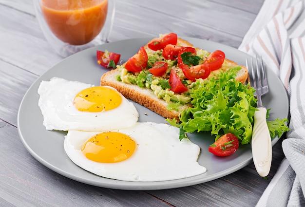 Huevo frito, ensalada de verduras y un sándwich de aguacate a la parrilla.