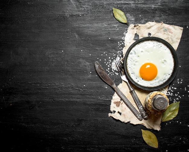Huevo frito con especias sobre un fondo de madera negra