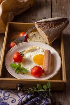 Huevo frito con hot dog y tomates