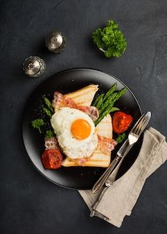 Huevo frito con pan tostado y espárragos.
