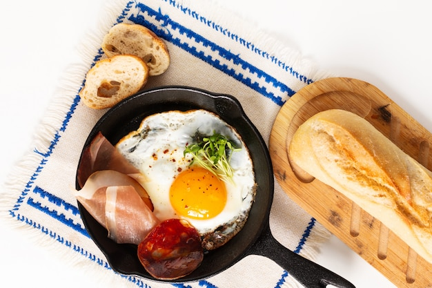 Huevo frito en sartén de hierro con brotes de lino y tocino con espacio de copia