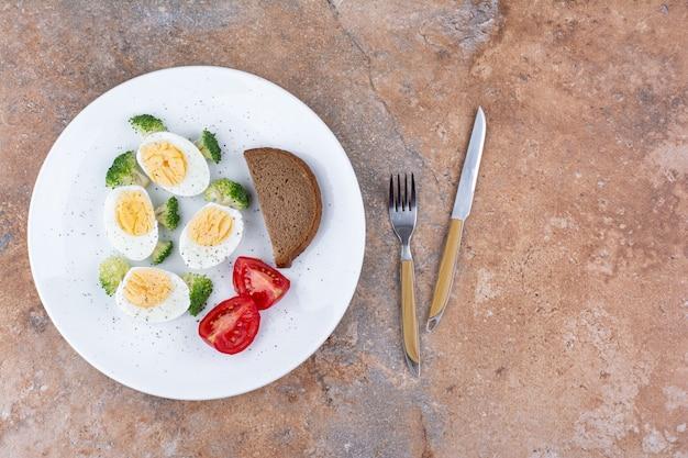 Huevo frito servido con tomates y hierbas