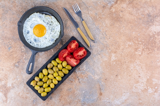 Huevo frito servido con verduras y aceitunas en bandeja de madera