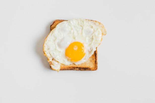 Huevo frito en una tostada aislada sobre fondo blanco