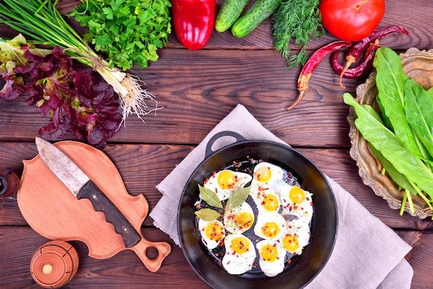 Huevo frito y verduras frescas y hierbas.