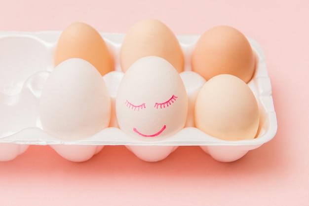 Huevo de gallina blanca con cara pintada y sonrisa en caja de huevos rosa. concepto de pascua feliz