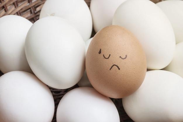 Huevo de gallina marrón con pintura en la emoción de la cara probada en la pila de huevo de pato blanco en el fondo de la cesta de madera