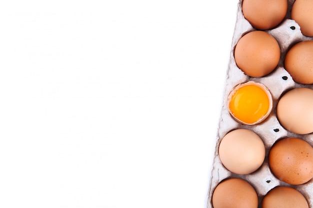 El huevo de gallina está medio roto entre otros huevos.
