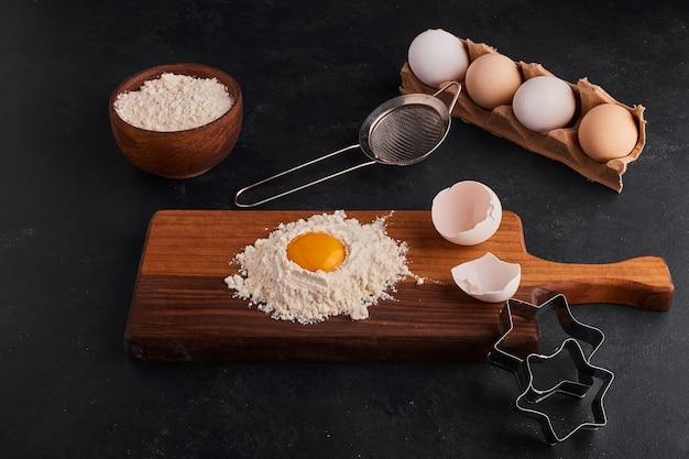 Huevo y harina mezclados entre sí sobre tabla de madera con forma de galleta alrededor.