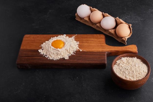 Huevo y harina mezclados entre sí sobre tabla de madera.