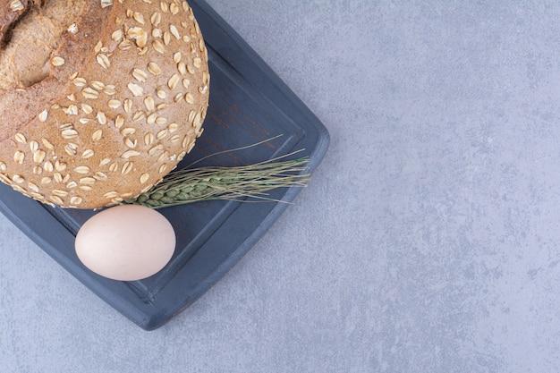 Un huevo, una hogaza de pan y un solo tallo de trigo en una tabla sobre una superficie de mármol