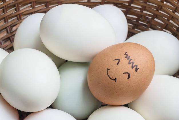 Huevo marrón del pollo del primer con la pintura en cara de la sonrisa en la pila de huevo del pato blanco