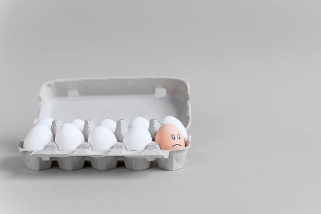 Un huevo de naranja con cara triste dibujada entre huevos blancos en una bandeja de cartón sobre fondo gris. diferente de otro.