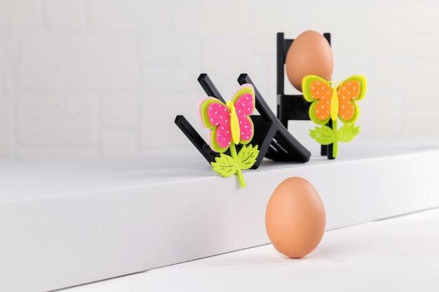 Un huevo natural sobre un fondo blanco y dos sillas negras con huevo y decoración de flores de pascua. minimale idea del concepto de pascua.