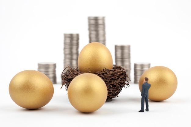 Huevo de oro y hombre de negocios sobre fondo blanco.