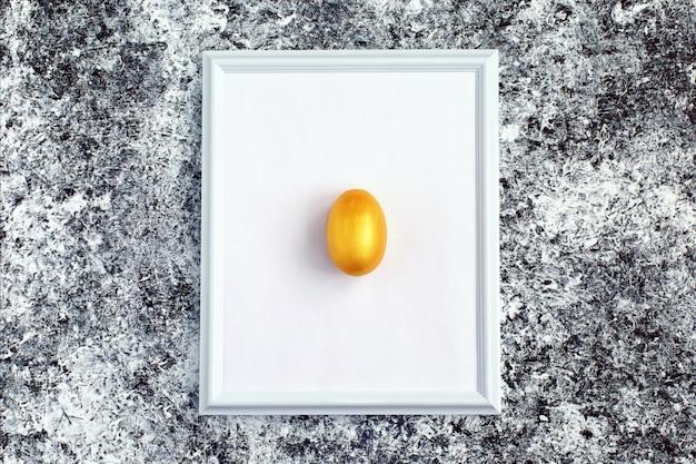 Huevo de oro sobre marco blanco