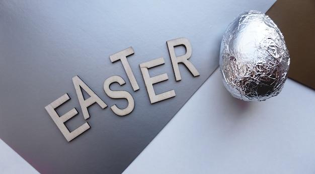 Huevo en papel de aluminio sobre fondo plateado. bandera del concepto de pascua. con texto pascua