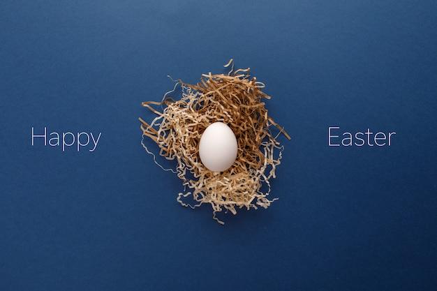 Huevo de pascua blanco con la palabra feliz de pascua, concepto de vacaciones. fondo azul.