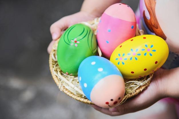 Huevo de pascua caza colorido en canasta en mano niña