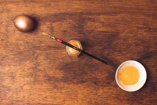 Huevo de pascua cerca de platillo y pincel sobre tinte